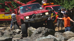 A small truck tries to get over a pile of boulders while a bystander gives - stock footage