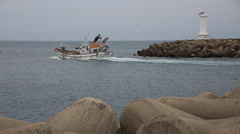Two fishing boats intersecting by the white lighthouse behind sea walls Stock Footage