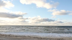 Dolly shot of winter sea and sandy shore with clouds time lapse Stock Footage