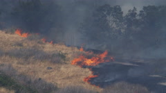 Dry grass blazes up at the edge of charred ground on a smoky hillside Stock Footage
