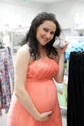 Young pregnant women looking for baby clothes in a store for their new babies. - stock photo