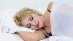Beauty lady waking up in her white bed and smiling Stock Footage