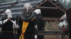 Brave warriors in medieval knight armour suits fighting with swords in the rain Stock Footage