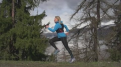 Woman Running Through Alpine Forest with Snow Capped Peaks in Distance. Stock Footage