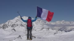 Mountaineer stands on peaks with the French Tricolour. Stock Footage