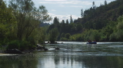A raft being paddled toward the camera on a peaceful stretch of the Rogue River, Stock Footage