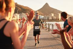 Young people encouraging runners at finish line Stock Photos