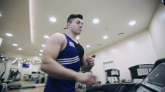 A man runs on a treadmill in the gym - stock footage