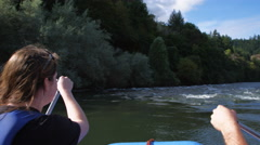 View from behind of a young woman paddling a raft through rapids on the Rogue Stock Footage