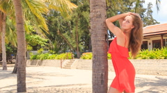 blond girl in red leans on palm trunk speaks against villa - stock footage