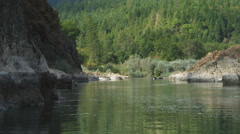 Drifting past canyon walls toward a forested hillside on the Rogue River, Oregon Stock Footage