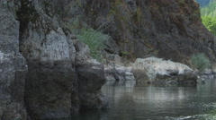 Drifting close past wall of Rogue River Canyon, Oregon; fish jumps near end of Stock Footage