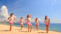 cheerleaders dance show varied poses on beach against sea - stock footage