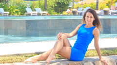 girl in blue sits bends leg on stone barrier against pool - stock footage