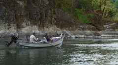 Close view of couple and dog in a drift boat on the Rogue River, Oregon Stock Footage