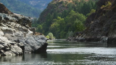Looking back upstream on a placid section of the Rogue River, Oregon Stock Footage