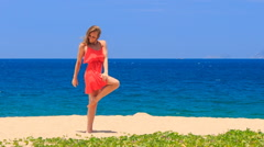 Blond girl in red dances barefoot on sand touches hip dress Stock Footage