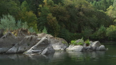 Floating past boulders at river's edge to reveal wooded shoreline Stock Footage