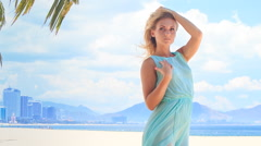 blonde girl in azure touches hair bust under wind on beach - stock footage