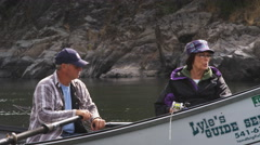 Close view of man and woman in drift boat on the Rogue River, Oregon Stock Footage