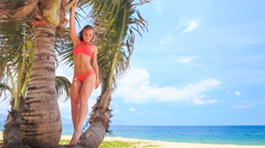 camera approaches to blond girl in bikini standing on palm - stock footage