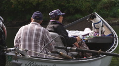 Close view of couple fishing from a drift boat while their dog sits in the prow Stock Footage