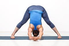 Woman doing yoga asana Prasarita padottanasana - stock photo