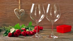 Valentines day's arrangements with red roses and two wine glasses over gray - stock footage