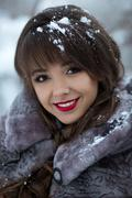 Beautiful portrait of smiling girl in winter forest with snowflakes on her hair - stock photo