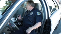 Police Officer with Radio in his hand speaks to another officer outside his pass - stock footage