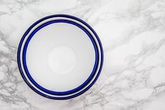 Big White Vintage Enamel Bowls on White Marble - stock photo