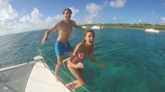 Cheerful couple jumping from boat into caribbean sea Stock Footage