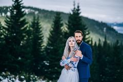 Groom in a blue suit and bride in white in the mountains Carpathians Stock Photos
