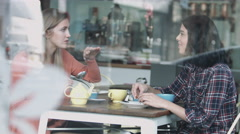 Female friends talking in coffee shop - stock footage