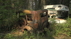 Stock Video Footage of auto junkyard in the forest, 1920s and camper med shot