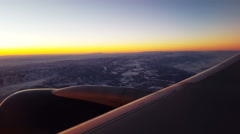 POV-Golden morning sun lights aircraft wing and horizon over snow mountains Stock Footage