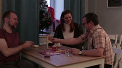 Two men and woman play a board game in a cafe Stock Footage