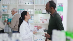 4K Worker in a chemist shop assisting mature gentleman Stock Footage