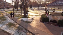 Aerial of couple walking through park at Christmas Stock Footage