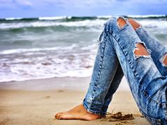 Legs of woman sitting on coast near ocean with waves. Hot dog leg selfie Stock Photos