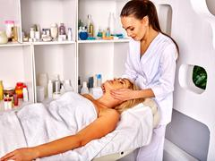 Woman middle-aged take face massage in spa salon - stock photo