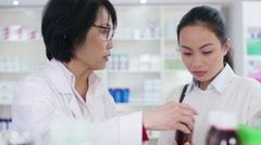 4K Friendly pharmacy worker advising young woman which medication to take - stock footage