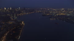 Flying up the East River in New York City at night, Empire State Building Stock Footage