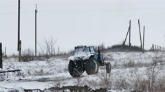 Tractor  slips stuck in snow on road winter Stock Footage