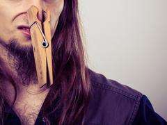Man with clogged nose by clothespin - stock photo