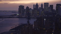 Stock Video Footage of Flying past Manhattan Bridge at dusk,  skyline of Financial District in