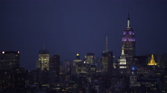Flying by Midtown Manhattan at night; Manhattan Bridge goes close through frame, Stock Footage