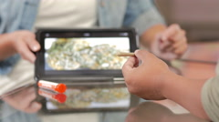 Customer at marijuana shop holding a joint and being shown product on a tablet Stock Footage