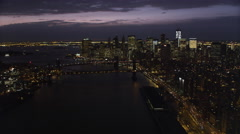 Flying high over East River at night, looking toward New York City Financial Stock Footage