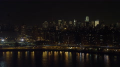 Low over the East River in Lower Manhattan at night, flying south; Financial Stock Footage